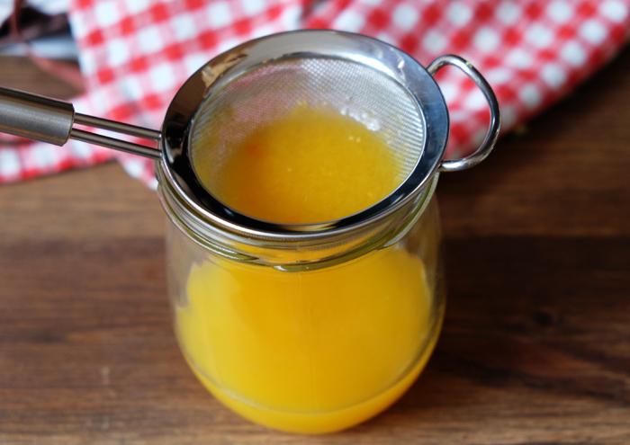 Orangensaft durch ein Sieb streichen