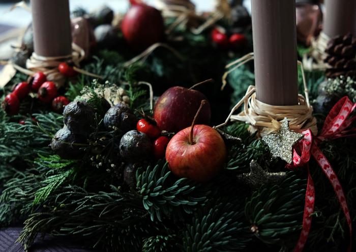 Mit roten Äpfeln und Beeren etwas Farbe in den Kranz bringen