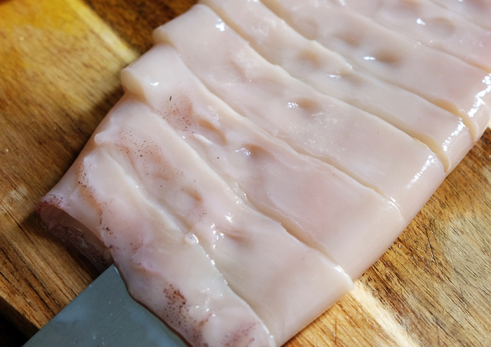 Mit einem zweiten Messer den Kalmar einschneiden